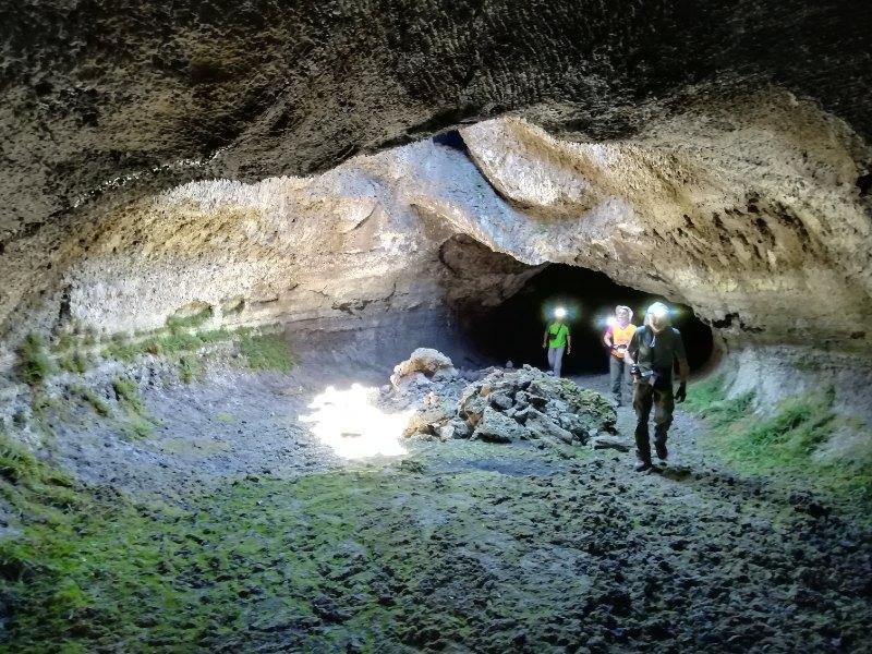 turisti che camminano dentro una grotta dell'etna