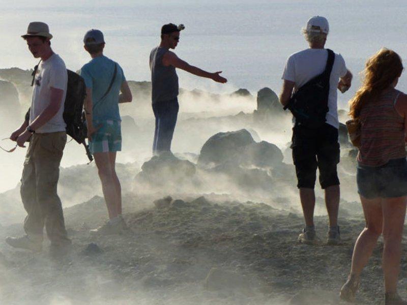 escursionisti che guardano le fumarole di vulcano