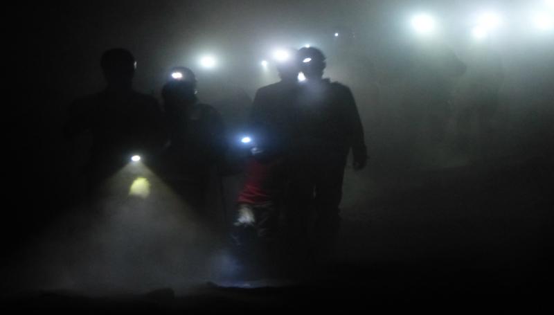 escursionisti che camminano di notte sul vulcano con la lampadina